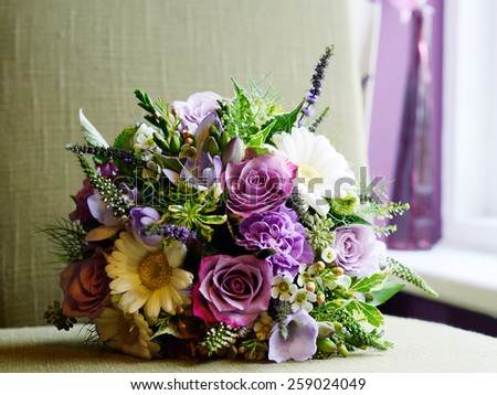 Brides bouquet with purple and white flowers on wedding day
