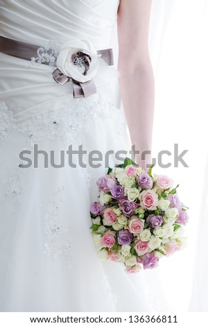 Brides dress detail and closeup of bouquet on wedding day - stock photo