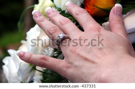 Brides hand showing an engagement ring on top of a bouquet.
