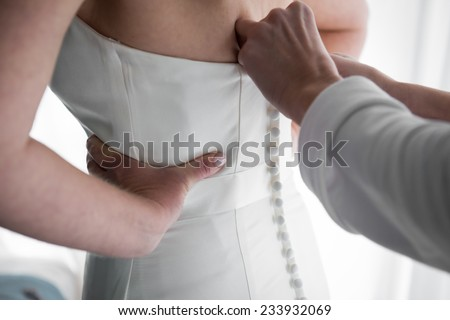 Brides maid helps bride dress in wedding dress for wedding day - stock photo