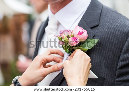bridesmaid adjusting flower on groom's jacket - stock photo