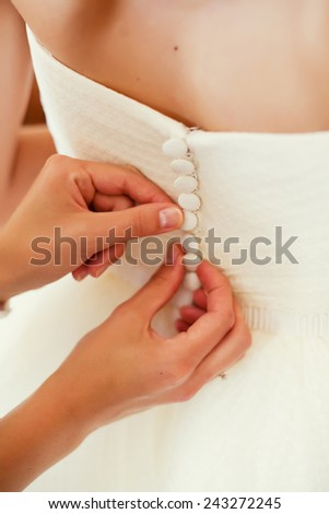 bridesmaid buttoning the dress on bride - stock photo