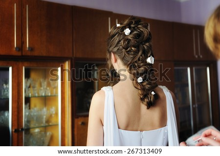 Bridesmaid helps the bride dress. - stock photo