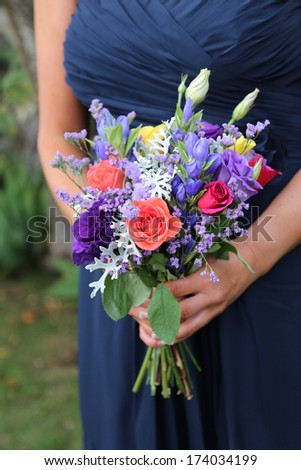 Bridesmaid holding a bright bouquet. - stock photo