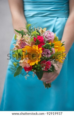 Bridesmaid holding colorful wedding bouquet against blue dress - stock photo