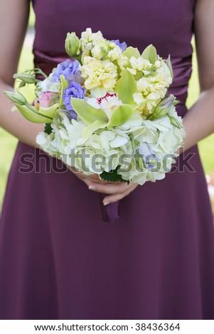 Bridesmaid holding colorful wedding bouquet against purple dress - stock photo