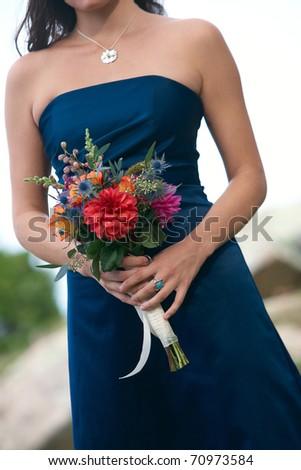 Bridesmaid holding wedding bouquet against blue dress - stock photo