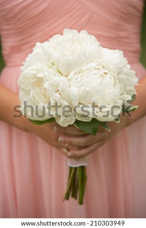Bridesmaid holding wedding bouquet of white carnations  - stock photo