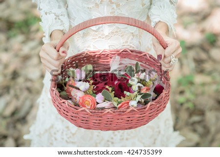 Bridesmaid in a white dress holding flower baskets for scattering rose petal at a wedding reception to church for a service of thanksgiving. - stock photo