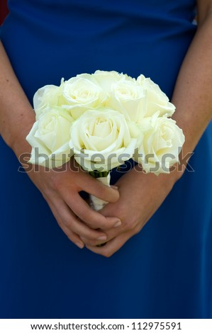 bridesmaid in blue dress holding a white rose wedding bouquet - stock photo