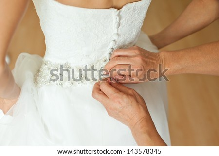 Bridesmaid is helping the bride to dress - stock photo