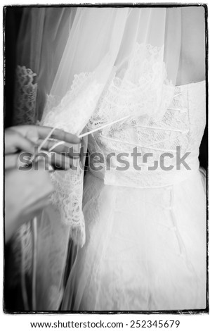 Bridesmaid is helping the bride to dress. closeup portrait of a maid of honor helping the bride with her dress. - stock photo