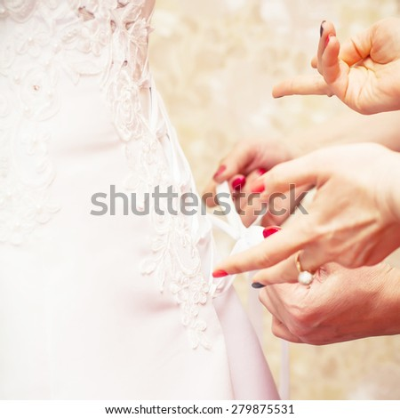 Bridesmaid is helping the bride to dress. WEddink theme background - stock photo