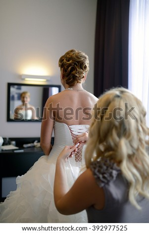 Bridesmaid is lacing white wedding dress for beautiful bride. Beauty model girl in bridal gown for marriage. Female portrait. Woman with curly hair and lace veil. Cute lady indoors - stock photo