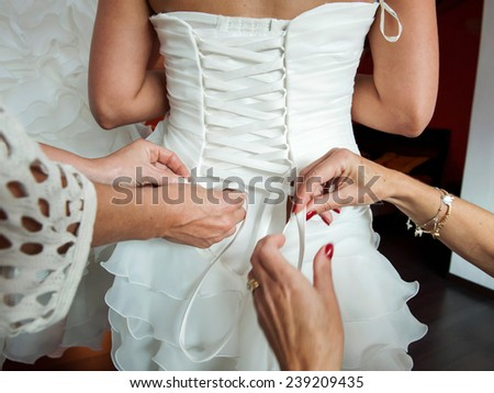 bridesmaid lacing back of wedding gown - stock photo
