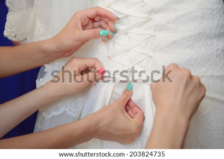 bridesmaid lacing up bride's wedding dress  - stock photo