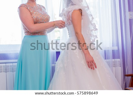 Bridesmaid wearing wedding dress to the bride