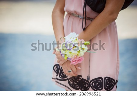 Bridesmaid with flower bangles. Focus on front flower. - stock photo