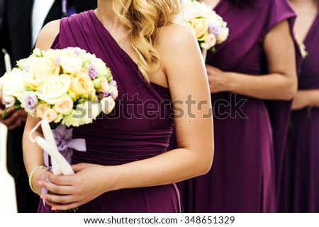 Bridesmaid with luxurious colorful wedding bouquet of roses and other flowers standing at the ceremony. - stock photo
