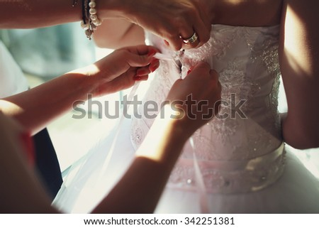 Bridesmaids helping beautiful bride put on dress tying laces  on white wedding dress - stock photo