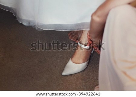 Bridesmaids helping young bride before the wedding ceremony dressed in a wedding gown and put on shoes - stock photo