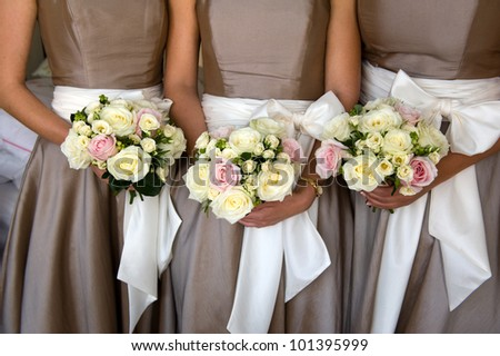 bridesmaids holding bouquet of flowers at a wedding - stock photo