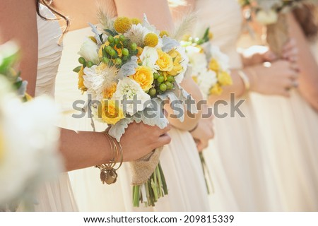 Bridesmaids holding bouquets during wedding ceremony  - stock photo