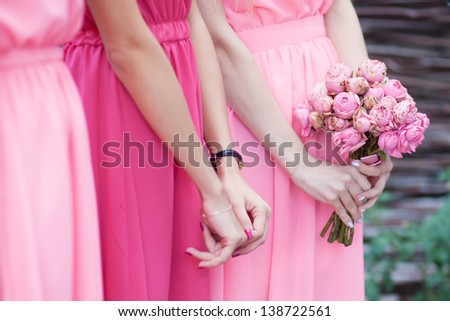 bridesmaids in pink dresses with a bunch of flowers - stock photo