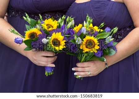 bridesmaids in purple dresses with sunflower bouquets - stock photo