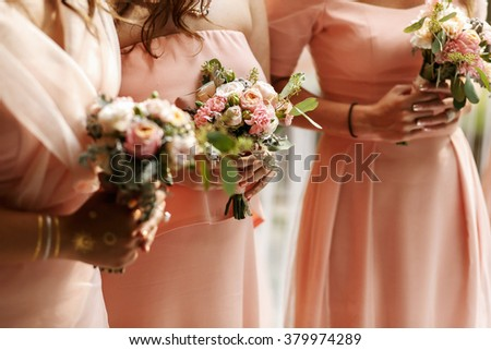 Bridesmaids with bouquet of flowers on the ceremony - stock photo