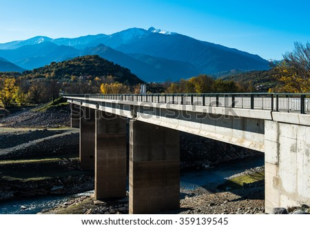 Bridge across the river in the French Pyrenees and picturesque mountain range - stock photo