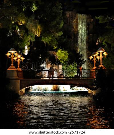 Bridge and waterfall at night - stock photo