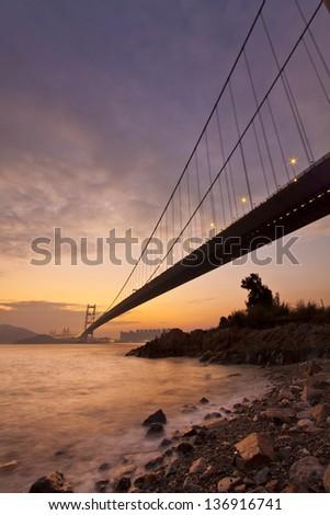 Bridge at sunset along coast - stock photo