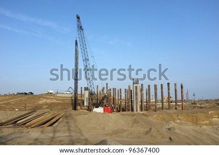Bridge Construction Project: Concrete columns are poured in place. Pile driver sets vertical steel pipes used to temporarily shore roadway. - stock photo