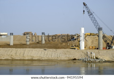 Bridge Construction Project: Concrete columns are poured in place. Reinforcing bars at the top will anchor into future horizontal structural members. - stock photo
