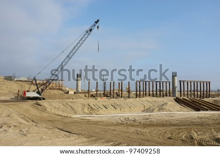 Bridge Construction Project: Concrete columns are poured in place. Vertical steel pipes are used to temporarily shore roadway. - stock photo