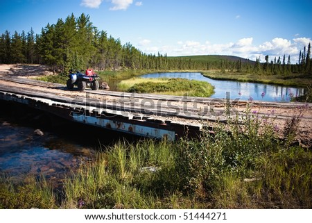 Bridge crossing on a Northern Canadian river in the thick evergreen forest. - stock photo