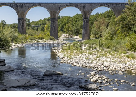 Bridge crossing the Ardeche river near the town of Vogue, France - stock photo