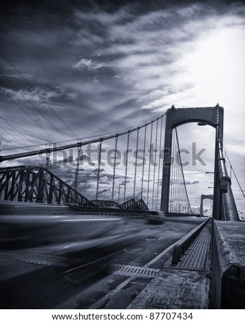 Bridge from canada with fast moving car on the road. Black and white with blue tint and vignetting added. - stock photo