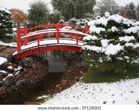 Bridge in Japanese garden near Normandale college in Minnesota during snowfall - stock photo