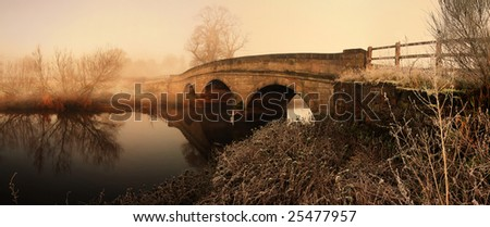 bridge in morning mist fog or haze. panoramic image of old stone construction - stock photo