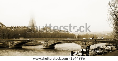 Bridge in Paris, France. Eiffel Tower just visible in the fog.  Movement on cars driving – Gloomy winters day. Copy space, Sepia Tone