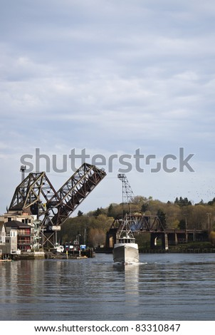 Bridge in Seattle opening to let a fishing boat pass - stock photo