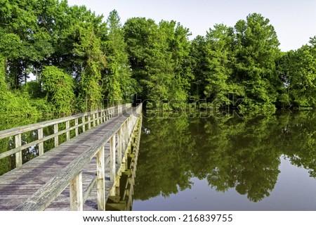 Bridge leading across a swamp in Decatur Alabama - stock photo