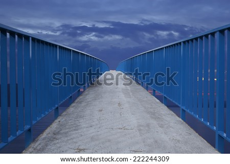 Bridge leading into the horizon against a surreal dramatic sunset. - stock photo