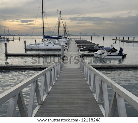 Bridge leading to dock with yatch - stock photo