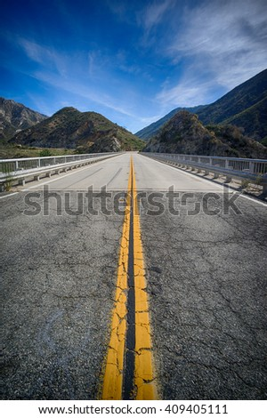Bridge leads over canyon in the mountains above Los Angeles California. - stock photo