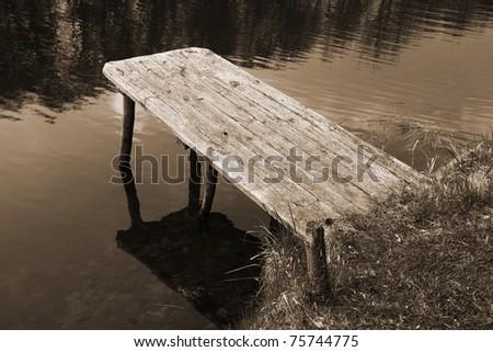 Bridge on a lake in sepia - stock photo