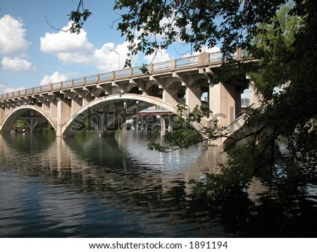Bridge on Lamar Blvd. over the colorado river in Austin, Texas. This bridge unites north and south Austin.   It has a beautiful calm view enjoyed by mainly hike and bikers on the trail. - stock photo