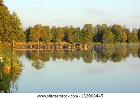 bridge on the lake in the rays of the rising sun - stock photo